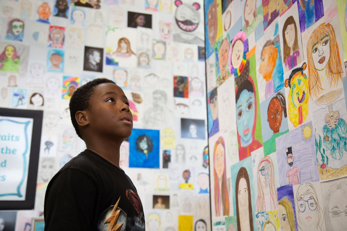 A student looks at a classroom wall which has been decorated with student artwork