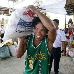 A man smiles as he receives relief goods from the Salvation Army in Tacloban, Friday, Nov. 22, 2013.