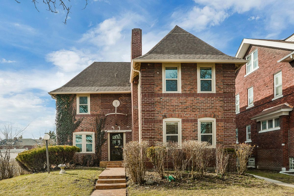 A brick home with a front entrance slightly set back. There's a few bushes out front.