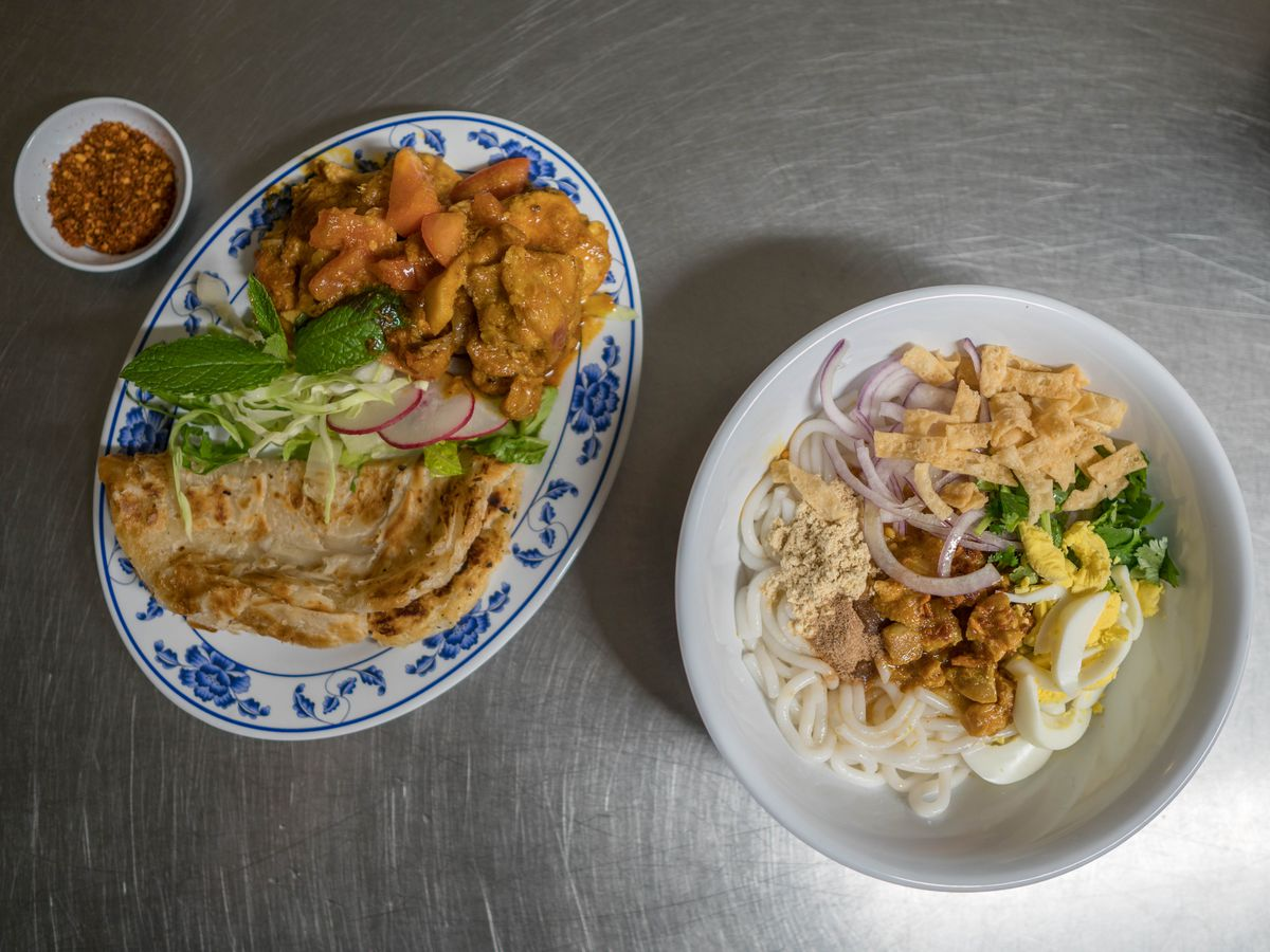 Two plates sit on a stainless steel table: a curried chicken dish with roti, and a udon-style noodle dish with eggs and onions