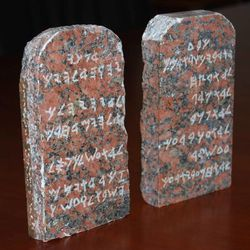 """One of the unique pieces from the Cecil B. DeMille collection are these small replica tablets of the Ten Commandments. The red granite comes from the heights of Mount Sinai, near the Red Sea, where the original Ten Commandments were given to Moses. DeMille retrieved the granite in 1954 while producing """"The Ten Commandments."""" When he returned to the United States, DeMille asked a professor at the University of Chicago to write a version of the commandments in early Canaanite lettering."""