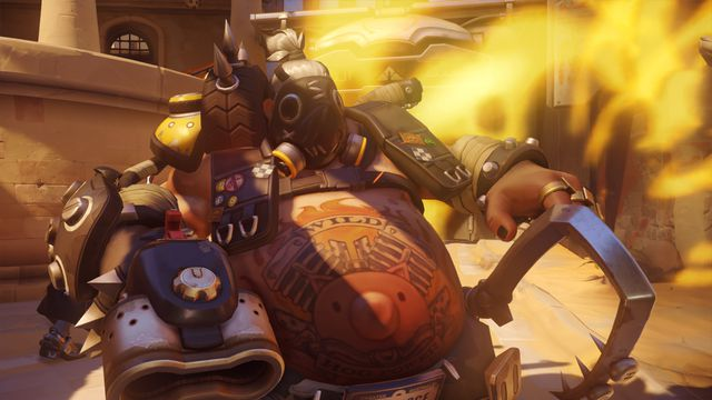 Overwatch - Roadhog lifts his chain and faces away from an explosive in the background