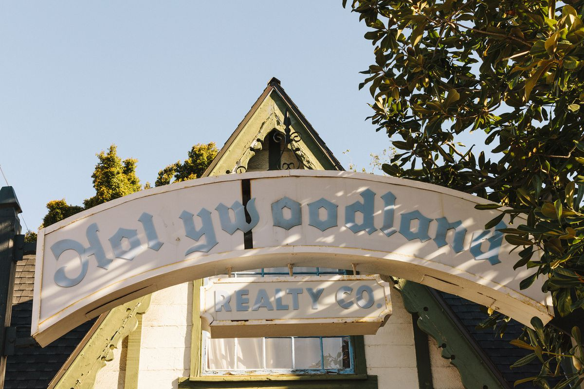 """A zoomed-in shot of an original sign and building for the Beachwood Canyon development in Hollywood. An arched wood sign spells out """"Holywoodland"""" (the second L is missing) and """"Realty Co."""" in blue font. The building's roof is pitched."""
