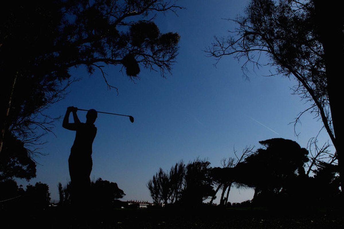 A golfist taking a golf swing on a golf course during a round of golf. Golf.