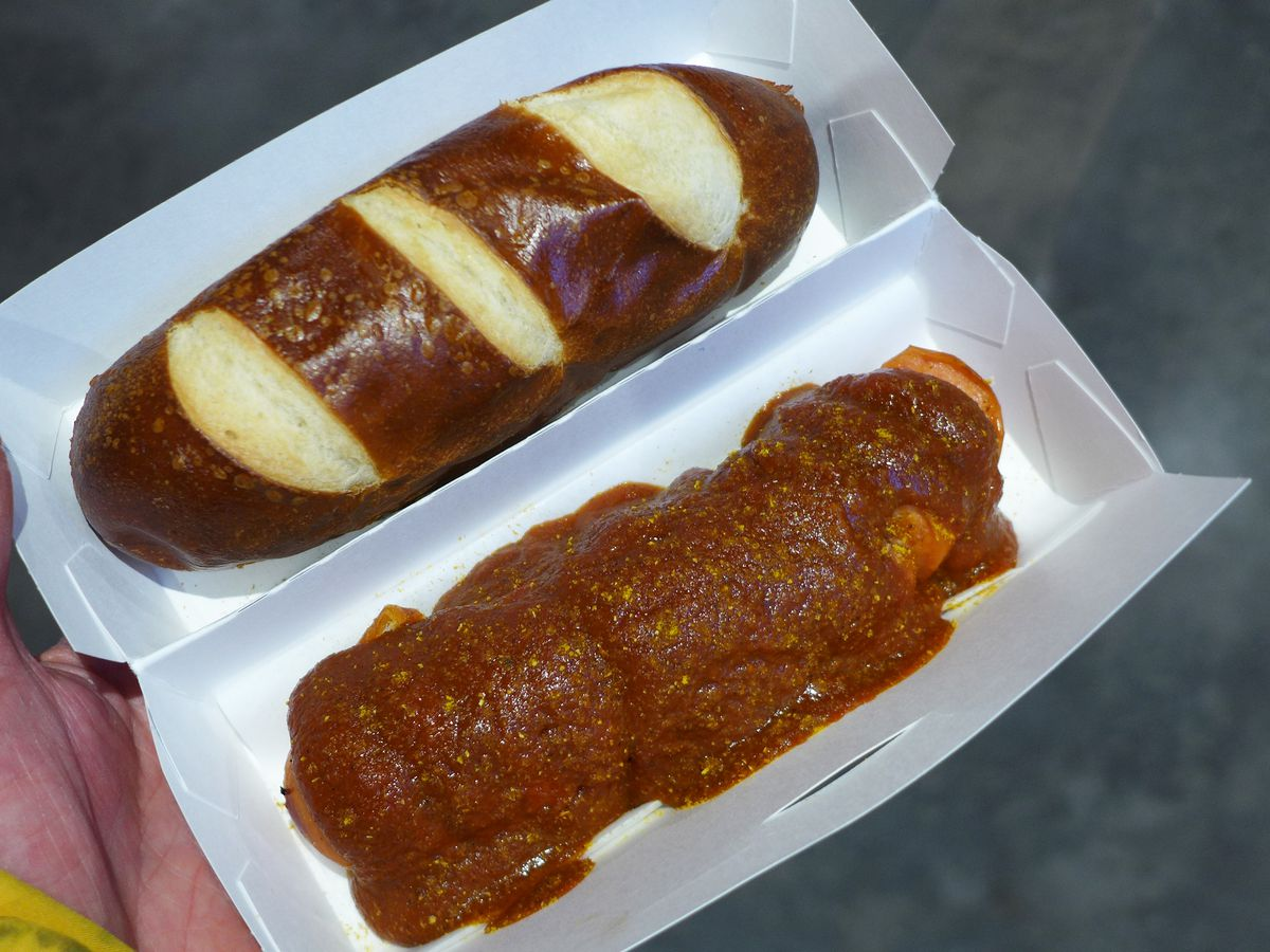 A linear brown pretzel bun with a curry smothered sausage beside it in a white takeout container.