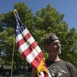 Army veteran Jeff Felt stands with the U.S. flag during the Salt Lake City Mission's Annual Fourth of July Picnic at Pioneer Park in Salt Lake City, Friday, July 4, 2014.