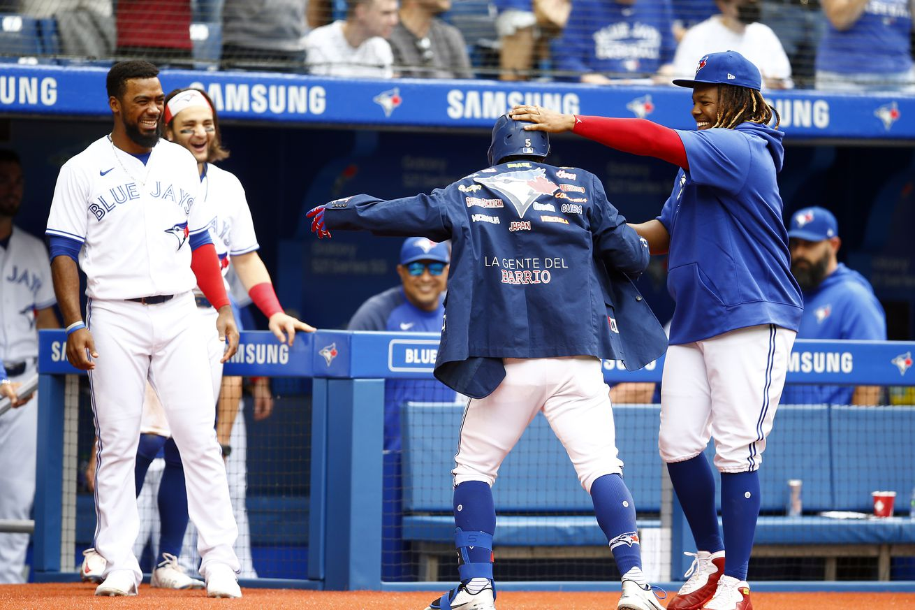 Santiago Espinal #5 of the Toronto Blue Jays receives the Blue Jays Home Run Jacket from Vladimir Guerrero Jr. #27 after hitting a home run in the fourth inning during a MLB game against the Kansas City Royals at Rogers Centre on August 01, 2021 in Toronto, Canada.
