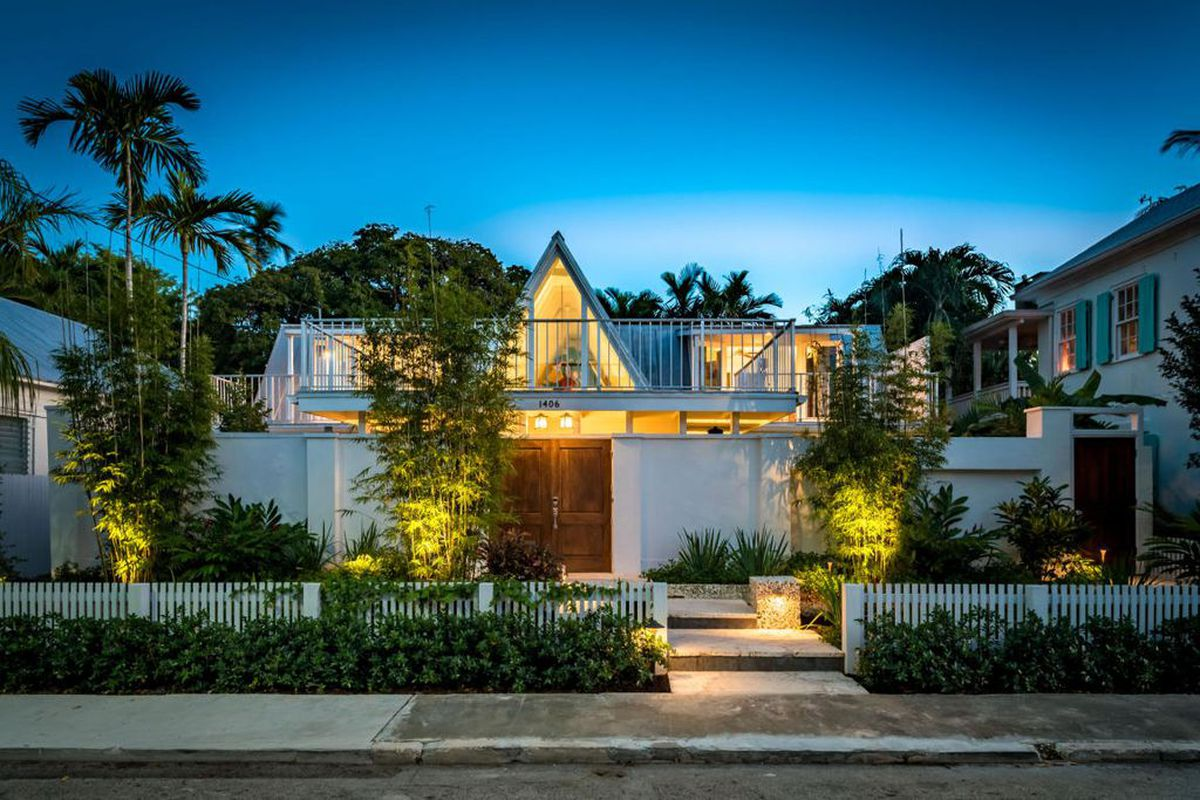 a frank lloyd-wright inspired home in key west with a pointed roof down the center and wooden door