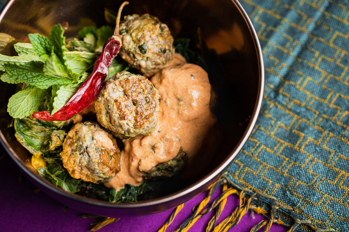 A dark bowl with light yellow sauce and meatballs and hot pepper inside.