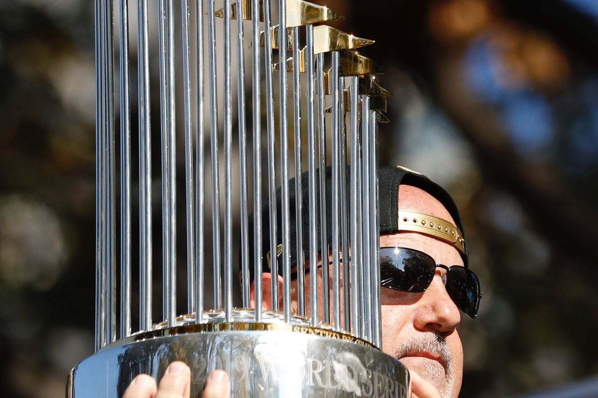 Washington Nationals general manager Mike Rizzo holds the Commissioners Trophy before the start of the World Series championship parade in downtown Washington, DC.
