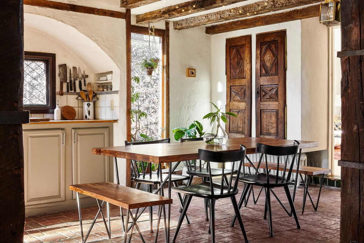A farmhouse-style kitchen features a dining table and bench with hairpin legs.