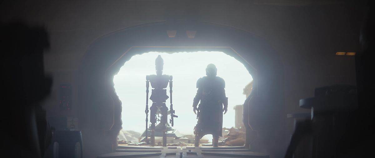 an IG-11 robot and the mandalorian stand in a cantina entrance backlit by the sun