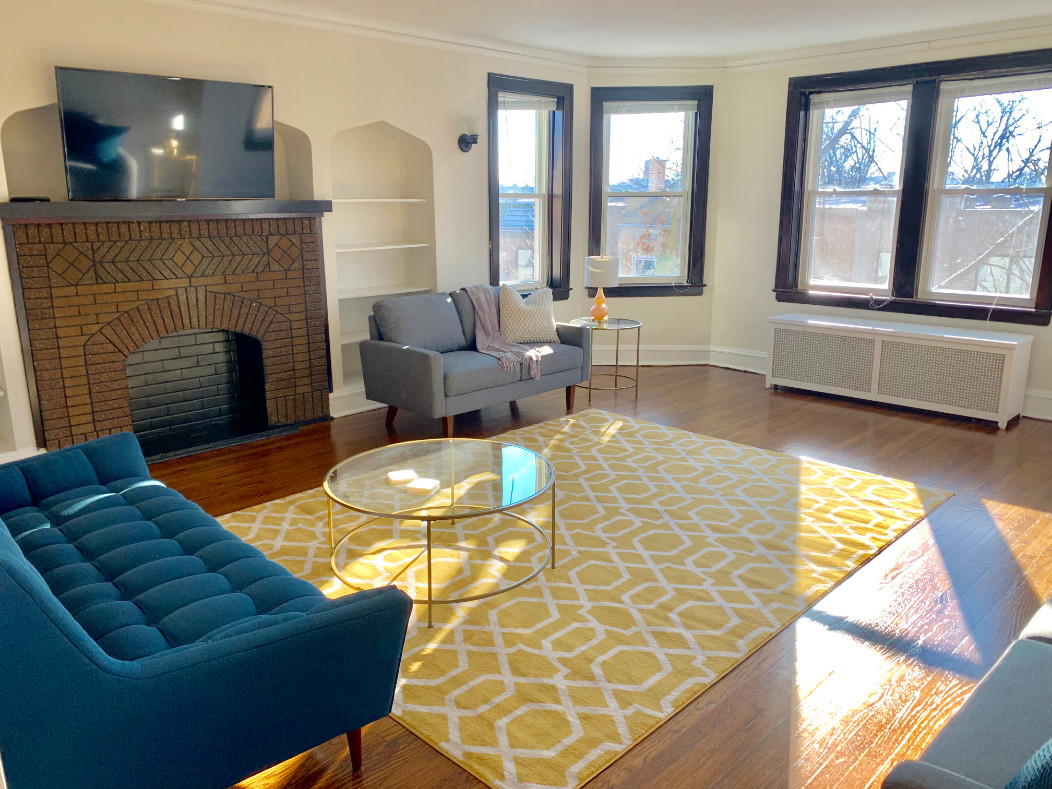 A living room with a large bay window, brick fireplace, and hardwood floor. There is a yellow area rug and a couch.