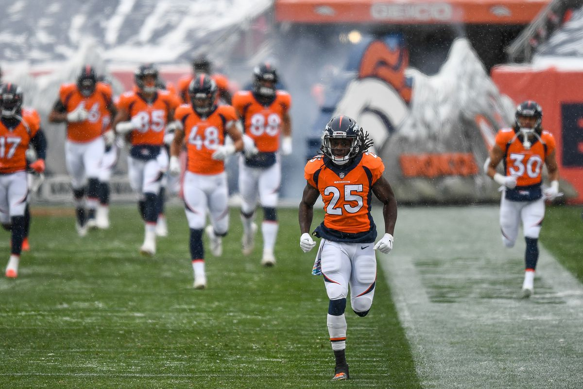 Denver Broncos players run onto the field behind Melvin Gordon #25 before a game against the Kansas City Chiefs at Empower Field at Mile High on October 25, 2020 in Denver, Colorado.