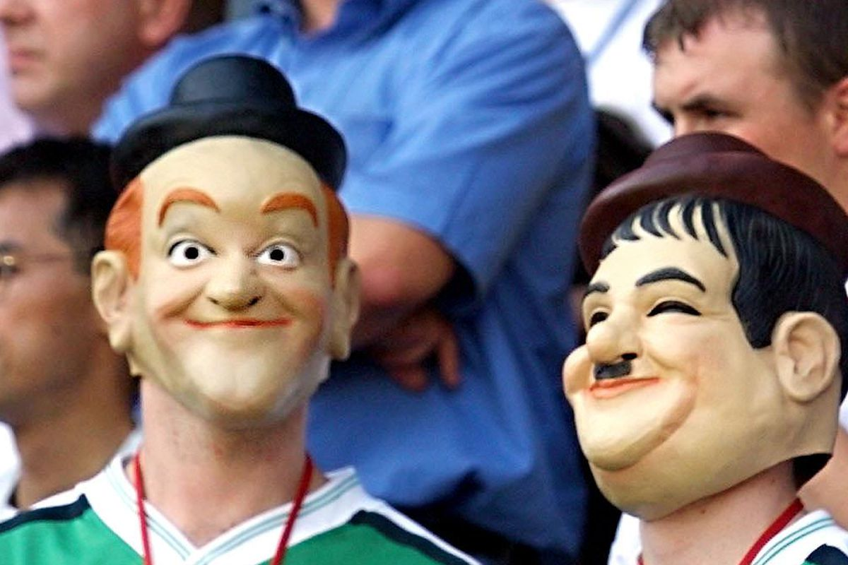 Two fans wearing masks of the famous comic actors