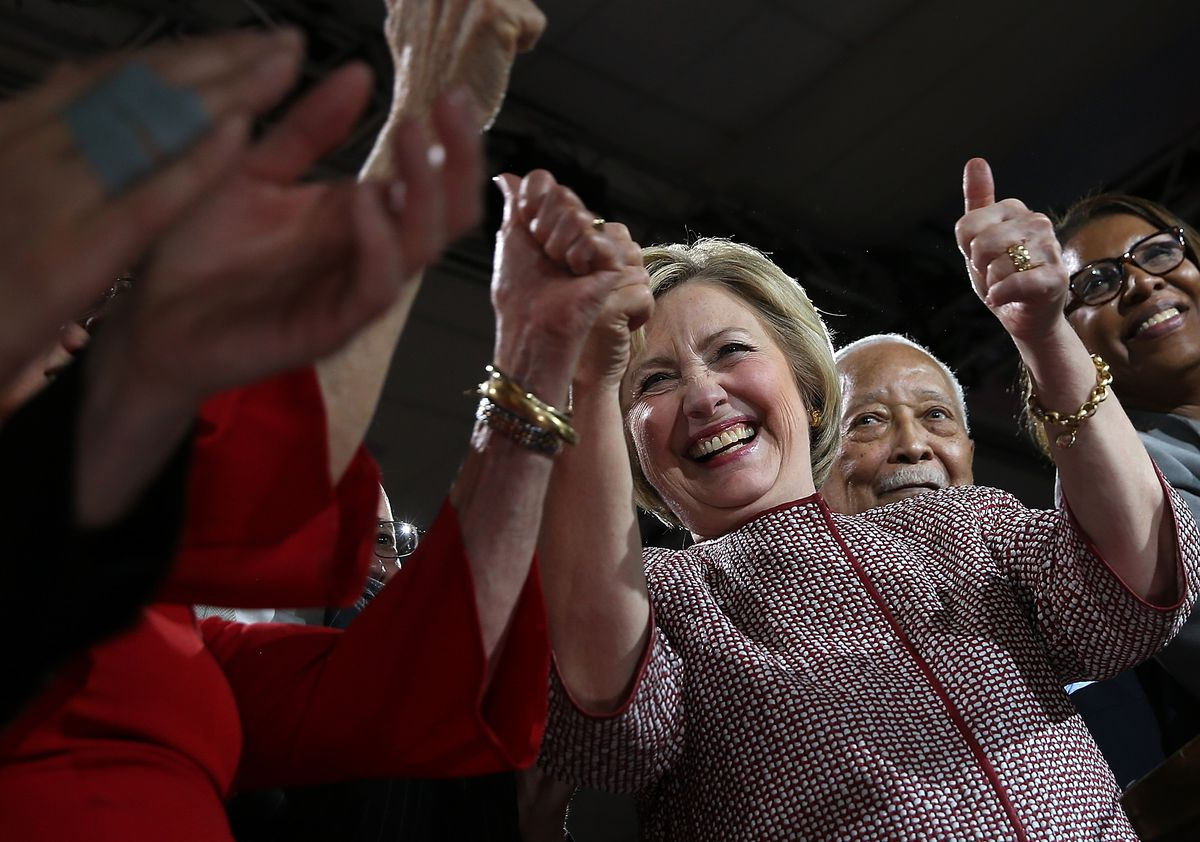 Clinton grinning with supporters' hands