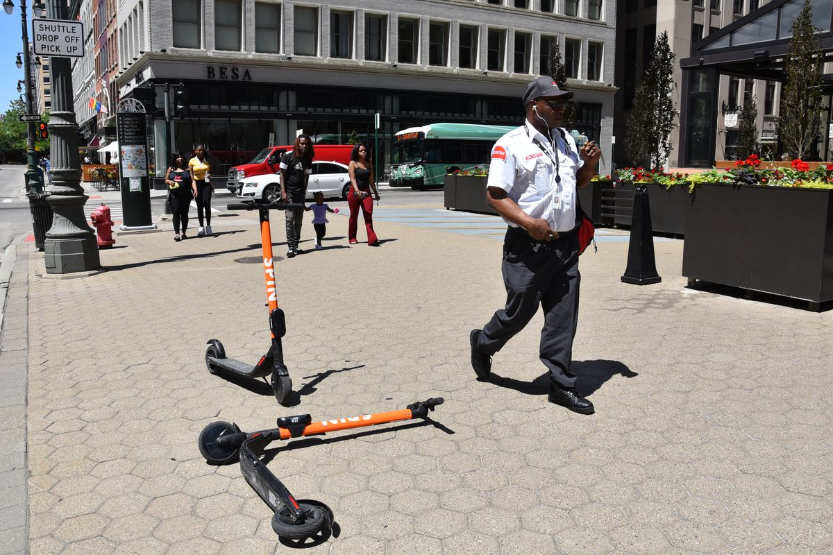 A security guard walks by two orange scooters on a sidewalk in Detroit.