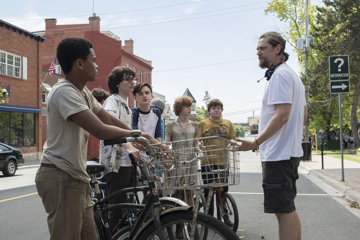 Muschietti stands in front of the younger cast of It, who are all on bikes.