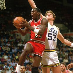 Mark Eaton goes after the block against young Michael Jordan during a 1984-85 season game.