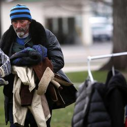 Chris Sanchez looks for coats at the 10th annual Community Coat Exchange at Pioneer Park in Salt Lake City on Friday, Nov. 28, 2014.