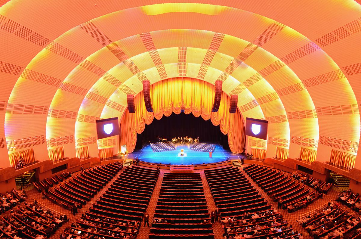The interior of Radio City Music Hall in New York City. There is a gold curtain above the stage and the ceiling and walls are curved.
