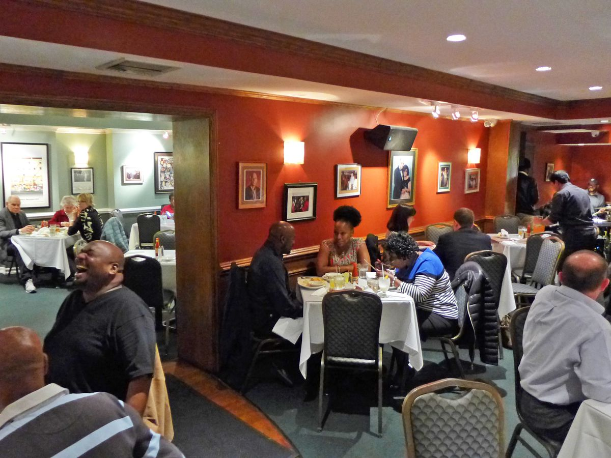 The packed dining room of Sylvia's with red walls