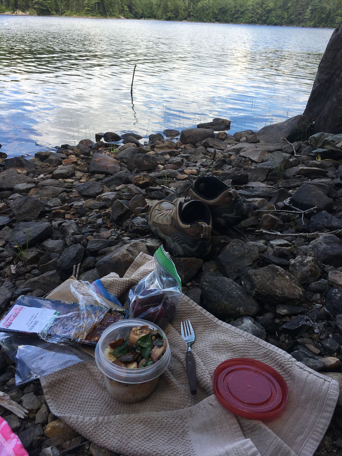 A picnic lunch on the shore of a lake, accompanied by a pair of hiking boots.
