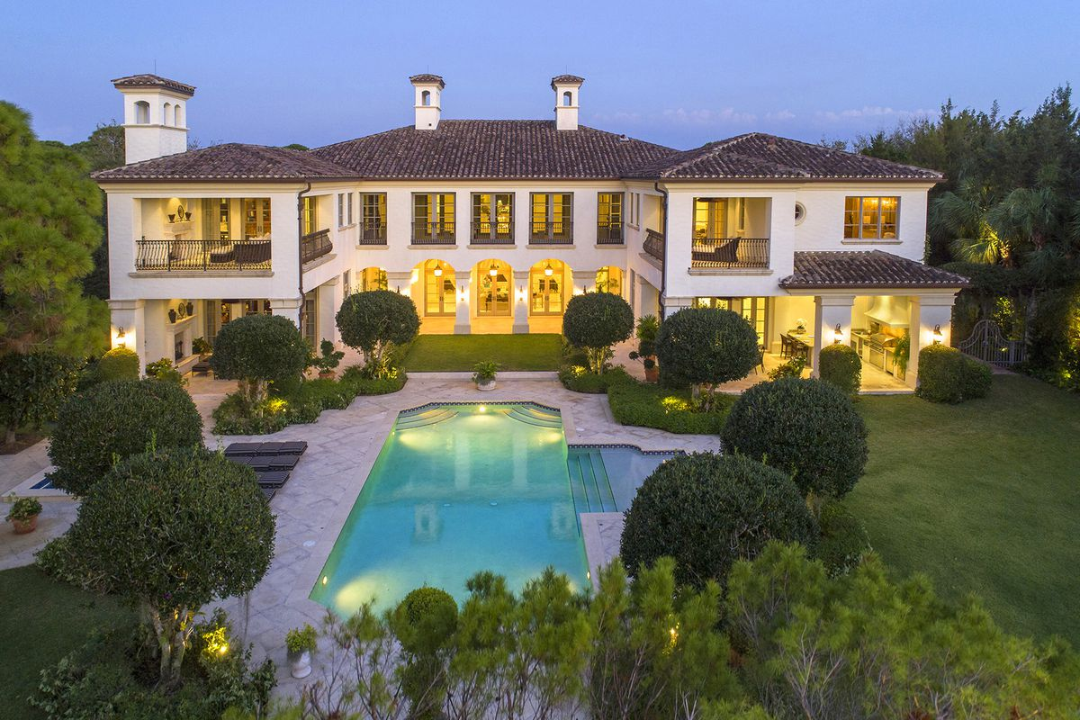 A large two-story estate with a brown roof, Mediterranean features, and an expansive pool set in front of a golf course and lushly landscaped yard