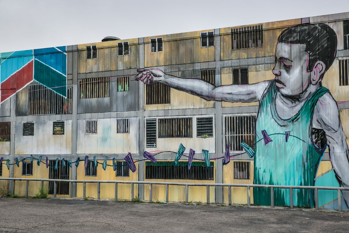 Large mural of a boy holding his hand over windows