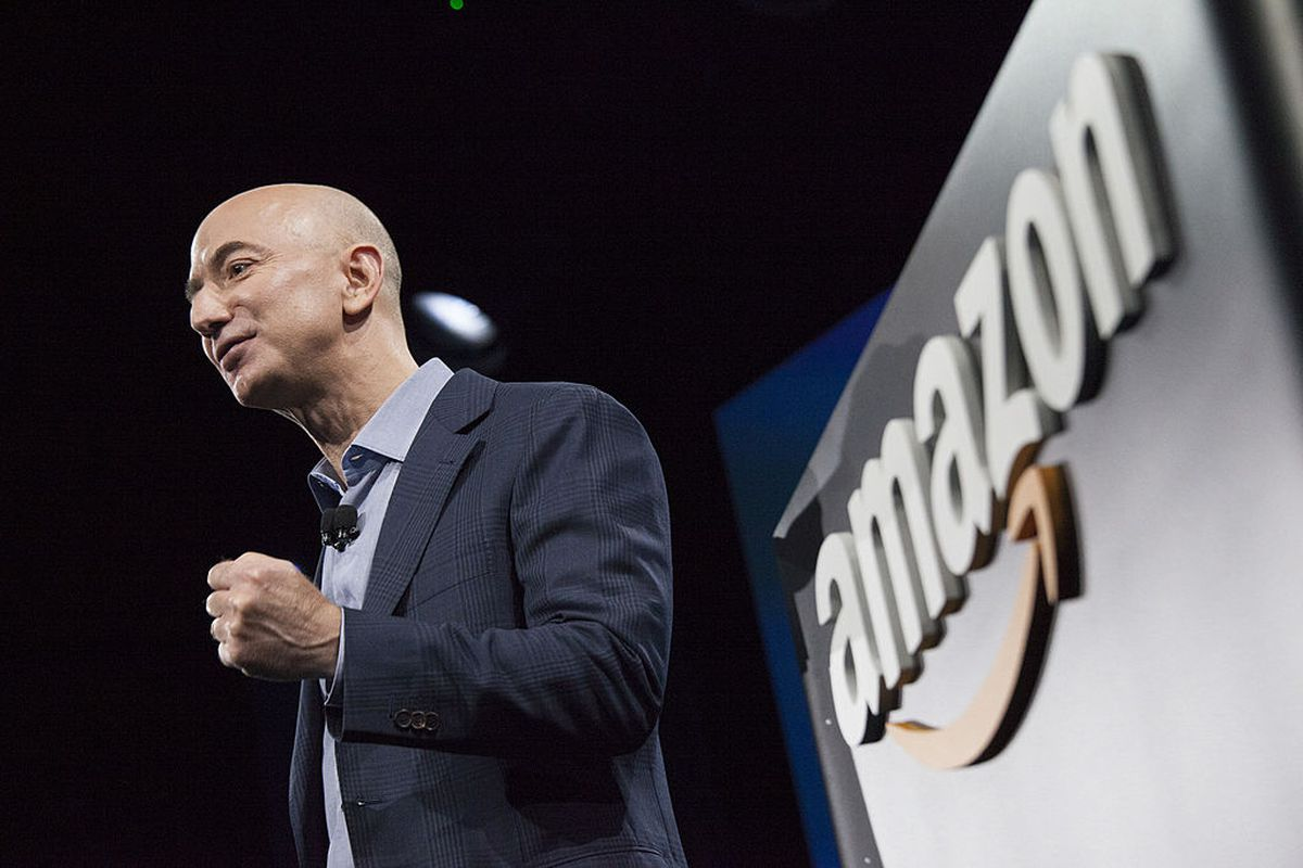 Bald man in jacket stands on stage in front of backdrop that says Amazon; it's the CEO, Jeff Bezos.