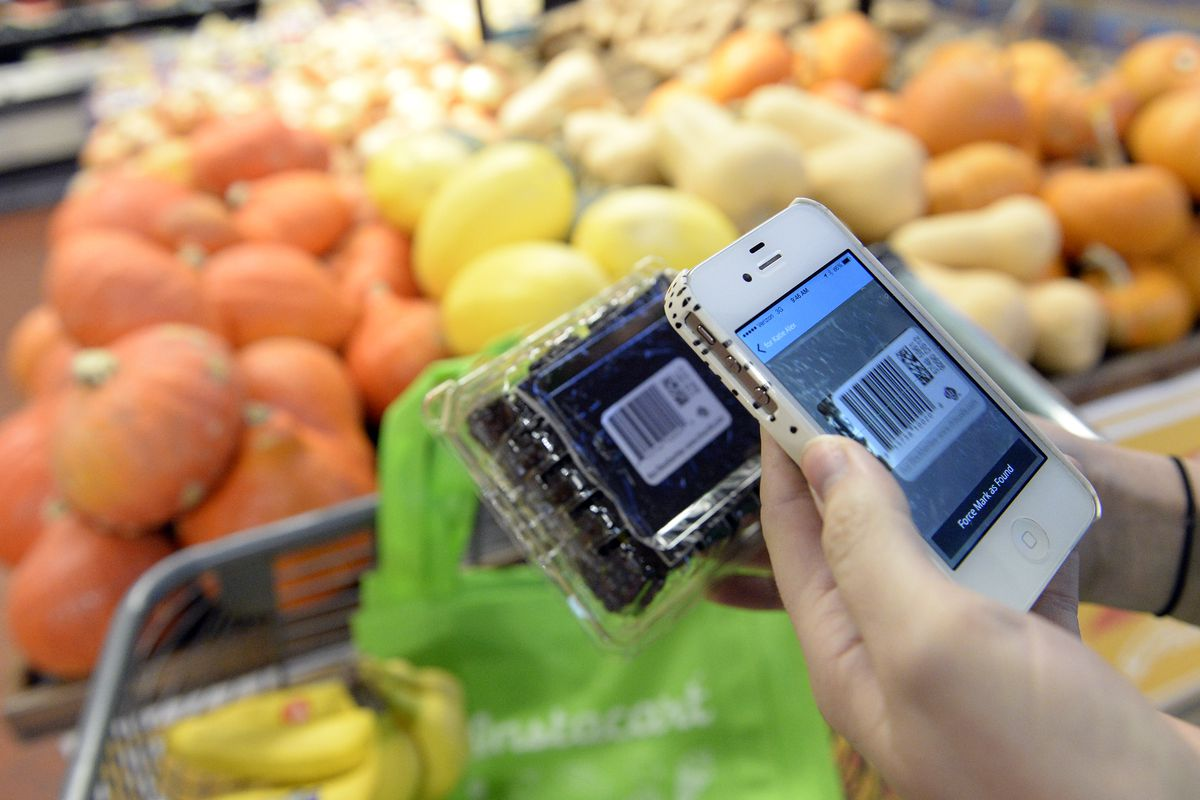 A shopper for Instacart uses the app while selecting produce