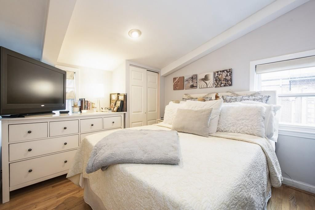 A bedroom with a bed facing a TV on a dresser.