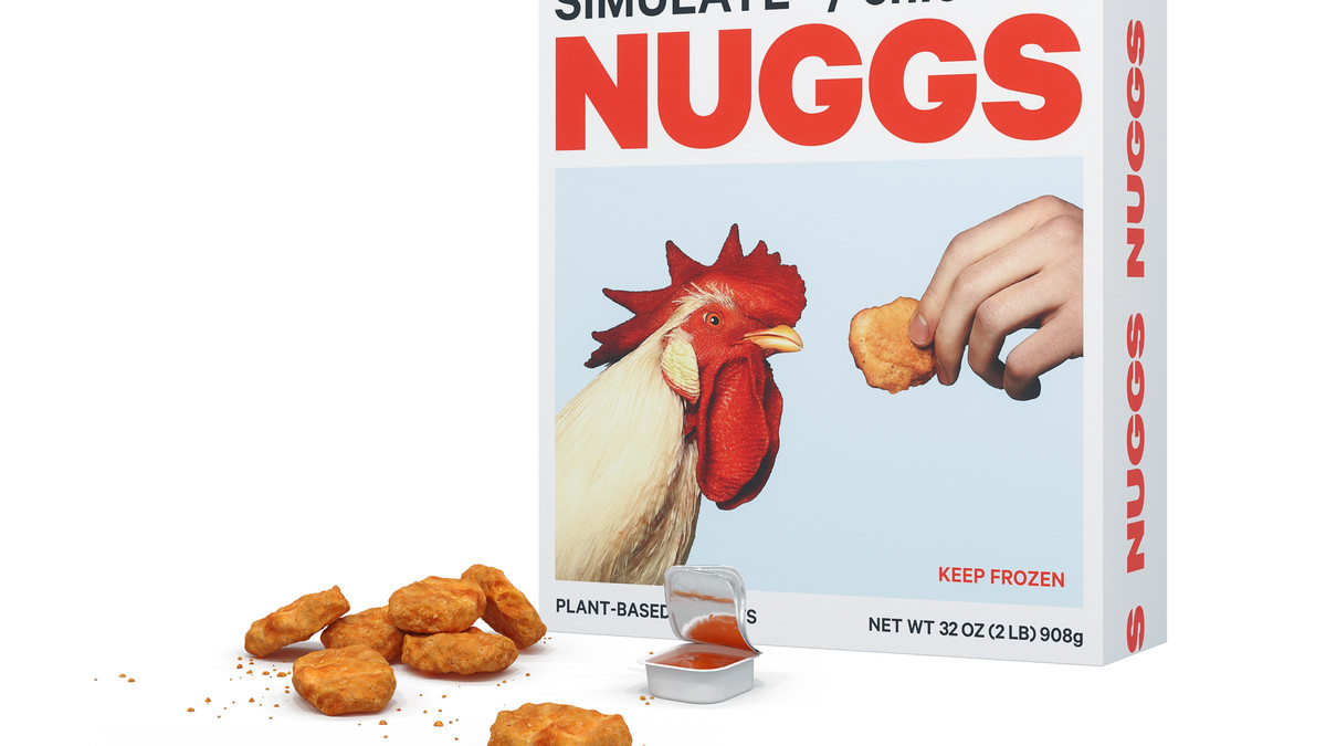 Some nuggets sitting in front of a Nuggs box, which has an image of a chicken being offered a nugget.