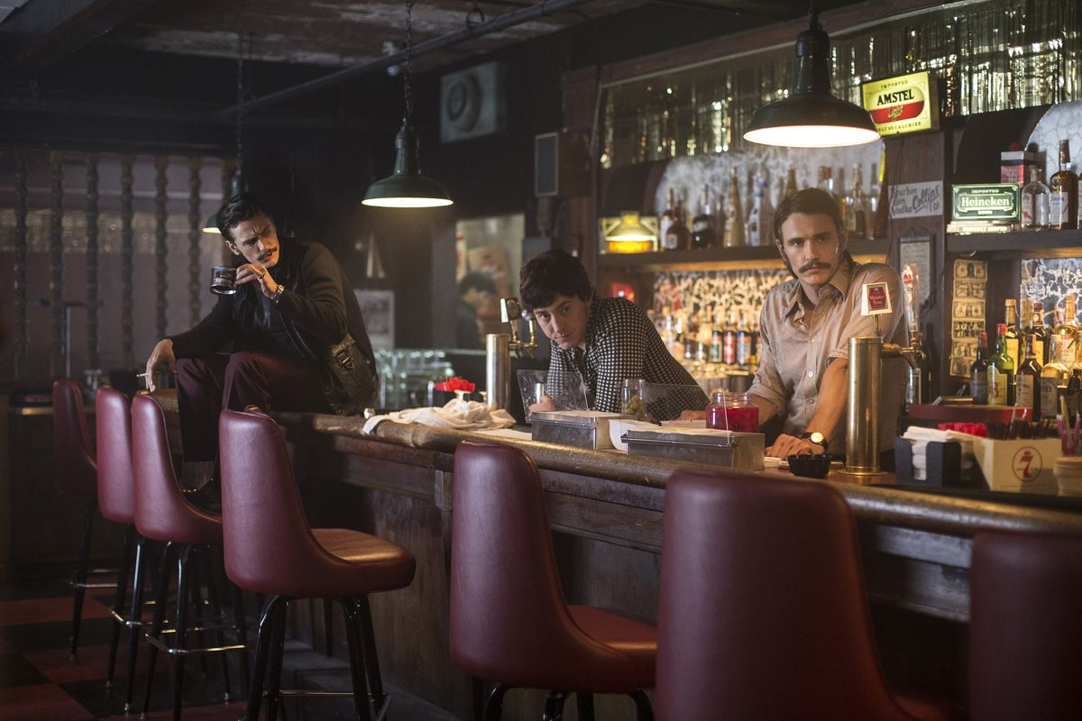 Still from 'The Deuce' showing James Franco's bartender character and two other men behind a bar