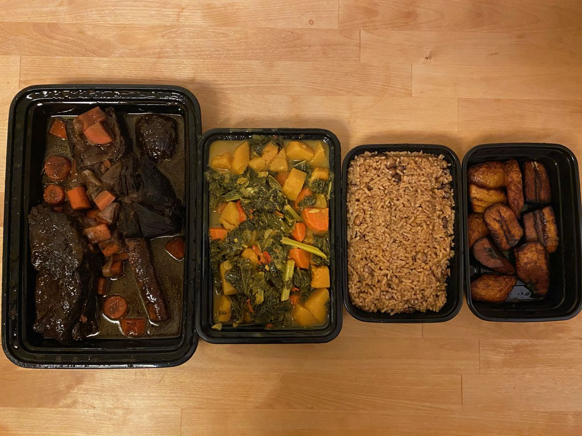 A set of black takeout containers filled with food lined up on a light wooden table
