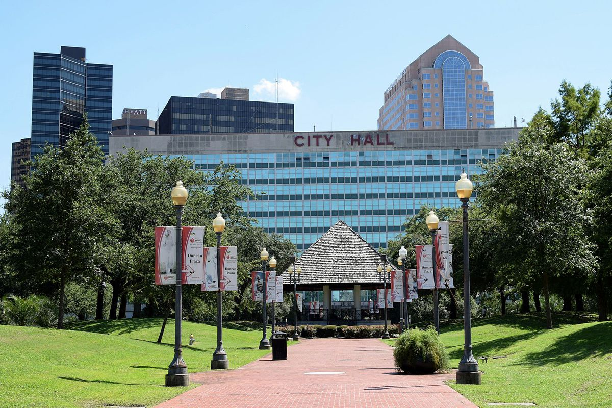 Reflective windows bounce sunlight off New Orleans City Hall behind a park lined with lampposts on a brick pathway