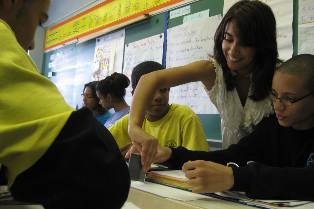 Blue Engine teaching assistant Alexandra DiAddezio helps 10th-grade geometry students with a project.
