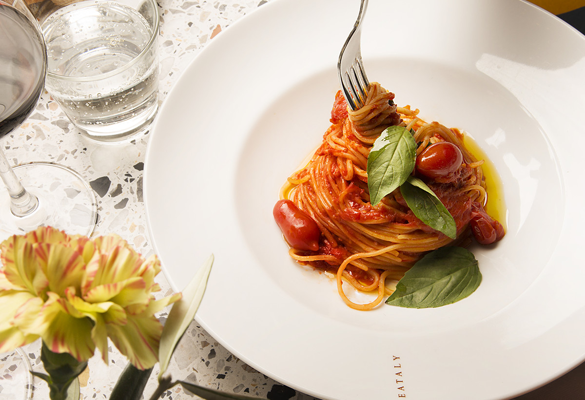 Spaghetti in a white dish, twirled around a fork with red sauce coating the pasta and basil draped across the top