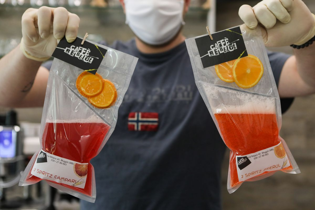 Gloved hands hold up bags of red takeaway cocktails.
