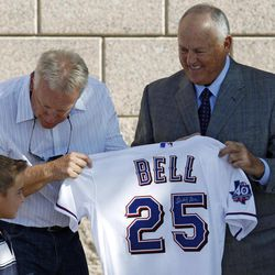 Cooper Stone, 7, receives a jersey, bat and ball by former Texas Rangers third baseman Buddy Bell, center, and Rangers owner Nolan Ryan, right, during the dedication for a statue of Shannon Stone, the fan who died after falling out of the stands trying to catch a ball in 2011, Thursday, April 5, 2012, in Arlington, Texas. The statue depicts Shannon with his son, Cooper, who he was with at the baseball game.