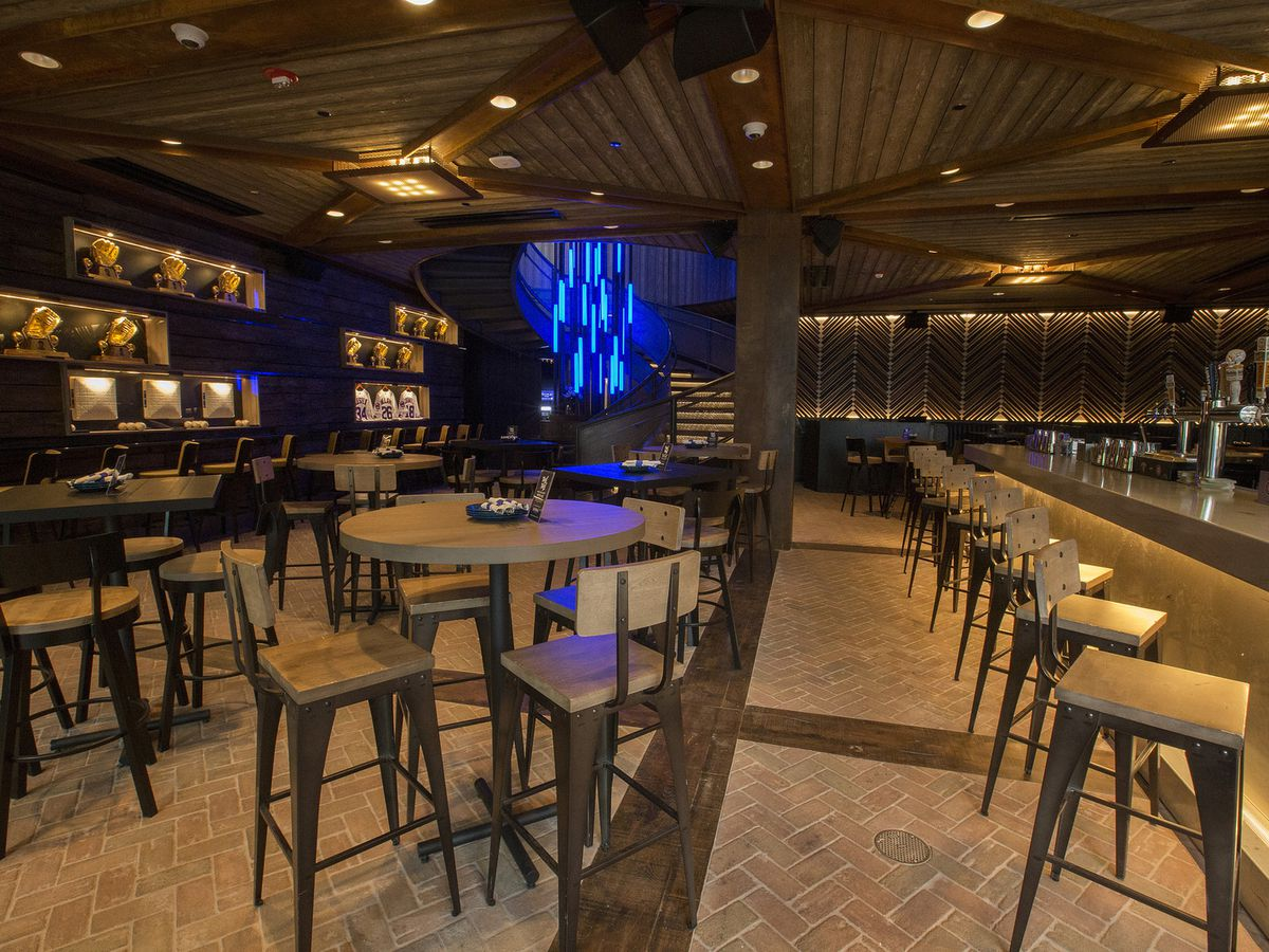 A bar space with exposed brick flooring, high-top tables and chairs, and warm yellow lighting. The space has a wood paneled ceiling and a glowing blue light fixture sits in a back corner.