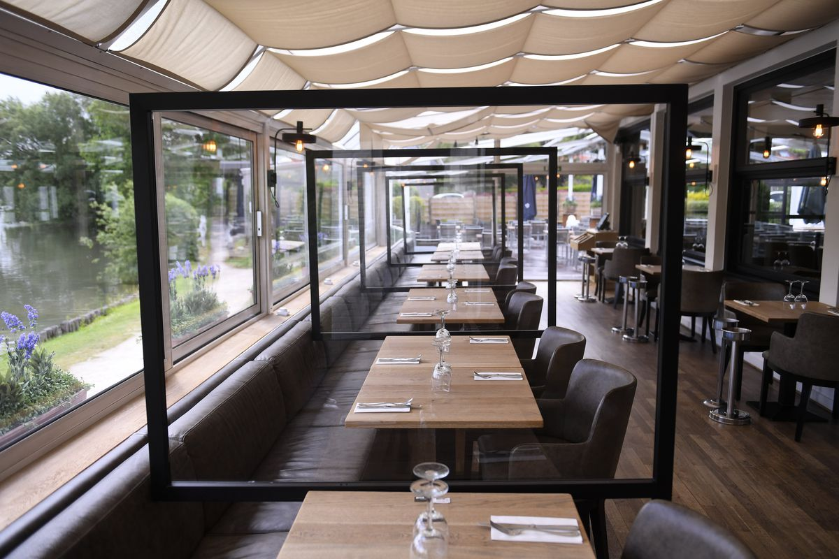 A restaurant in Belgium erects clear plastic barriers between tables in preparation for its reopening.