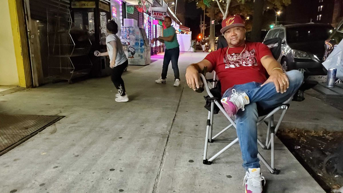 """Tommy Tejada, 36, enjoyed a beer with friends on the Prospect Avenue sidewalk in the South Bronx after hearing the news that Biden was projected to win the presidency. The 36-year old owner of a welding business said he was happier than ever. The group danced to bachata and chatted from their fold out chairs about """"everything but Trump."""""""