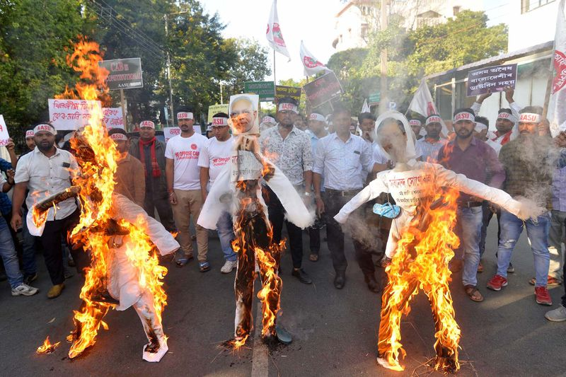 Activists from All Assam Students Union burn effigies of India's Prime Minister Narendra Modi and others associated with the Citizenship Amendment Bill.