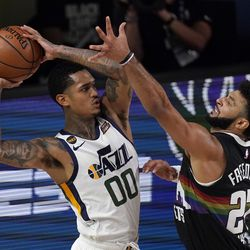 Utah Jazz's Jordan Clarkson (00) works to make a pass as Denver Nuggets' Jamal Murray (27) defends during the first half an NBA first round playoff basketball game, Tuesday, Sept. 1, 2020, in Lake Buena Vista, Fla.