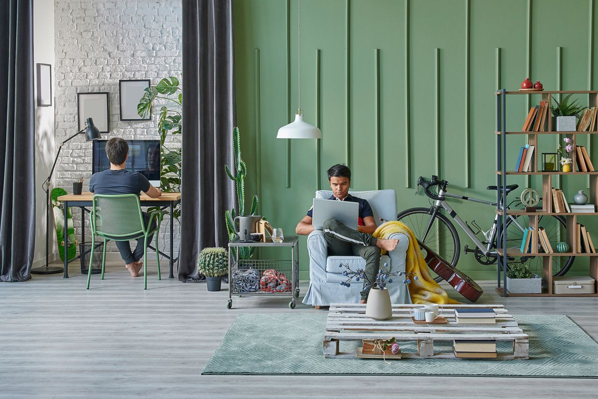 Two young men are on computers in a  green apartment.