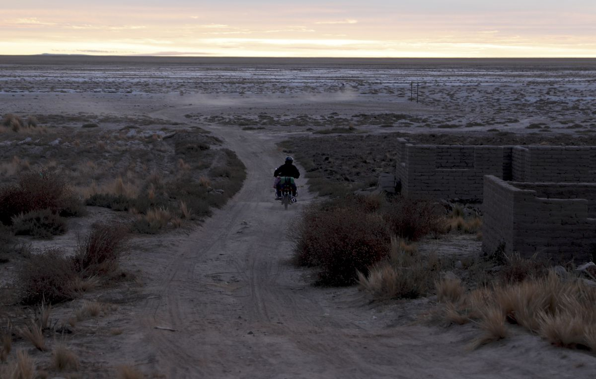 A man drives his motorcycle on a dirt path along the salt-crusted former shoreline of Lake Poopo, in Punaca, Bolivis. For many generations, the homeland of the Uru wasn't land at all. It was the brackish waters of Lake Poopo.