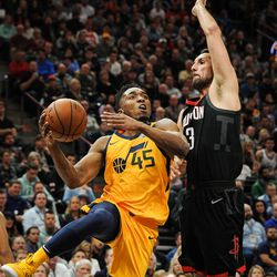 Utah Jazz guard Donovan Mitchell (45) drives the lane and dishes the ball around Houston Rockets forward Ryan Anderson (33) as the Utah Jazz host the Houston Rockets at Vivint Smart Home Arena in Salt Lake City on Thursday, Dec. 7, 2017.