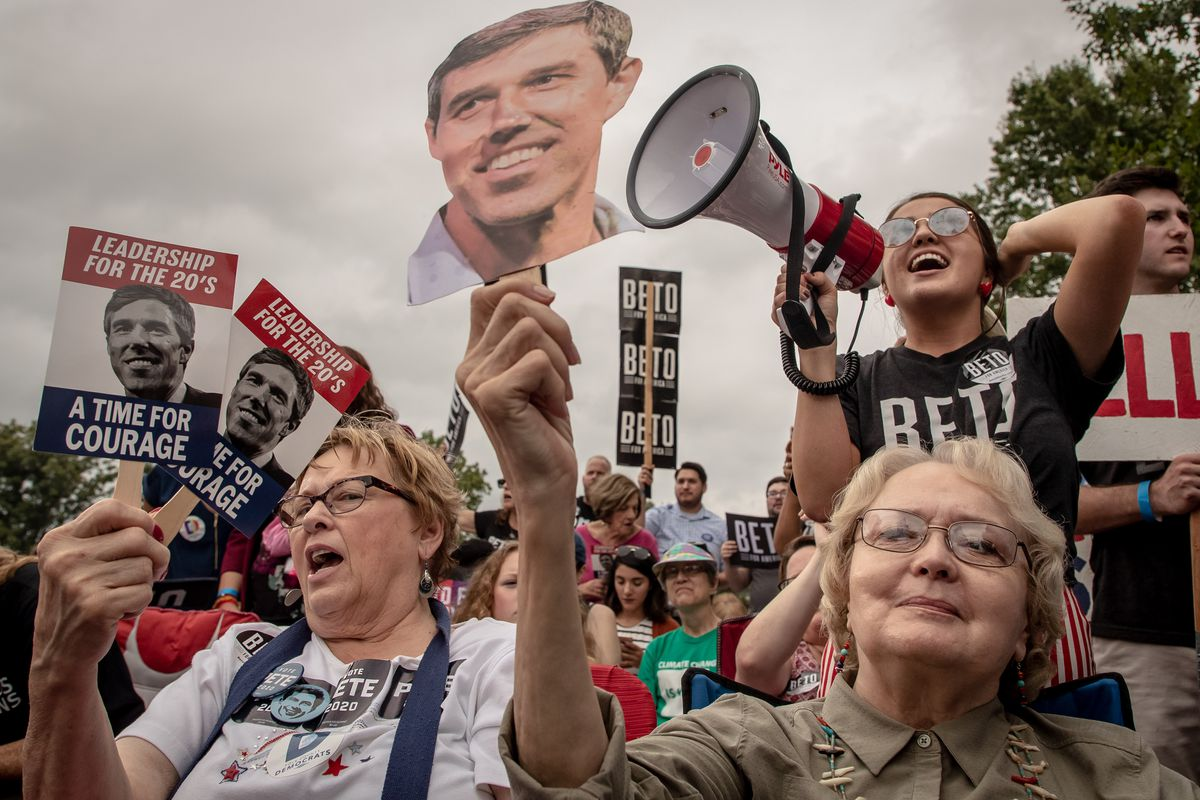 A crowd of supports holds signs featuring Beto O'Rourke's face.