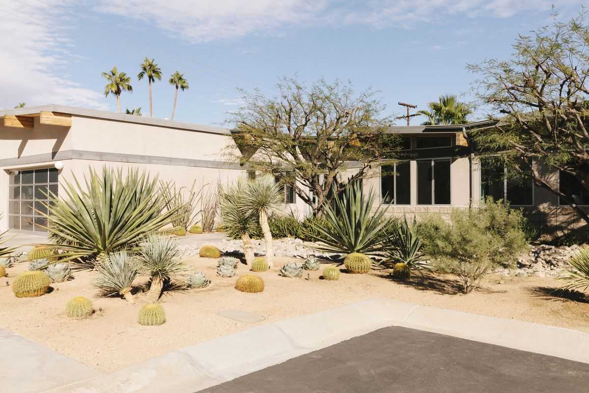 A house which is one level. It has windows and is painted a light tan color. There are desert plants in front of the house.